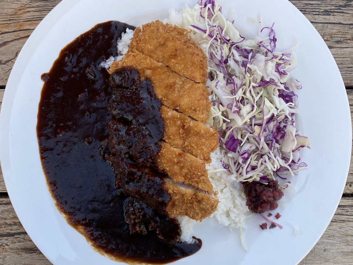 A white plate with rice, shredded cabbage, and pork tonkotsu topped with inky black curry.
