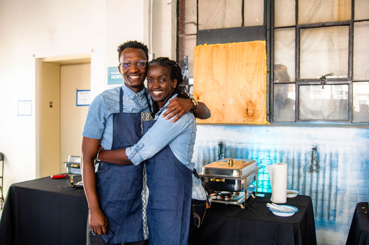 A couple in matching aprons and shirts poses in an embrace.