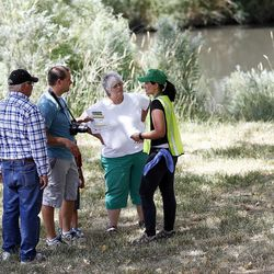 Susan Collier, of Salt Lake City Community Emergency Response Teams, talks with the Brent James family in Salt Lake City on Monday, July 18, 2016, warning them of possible toxic algae contamination in the Jordan River.
