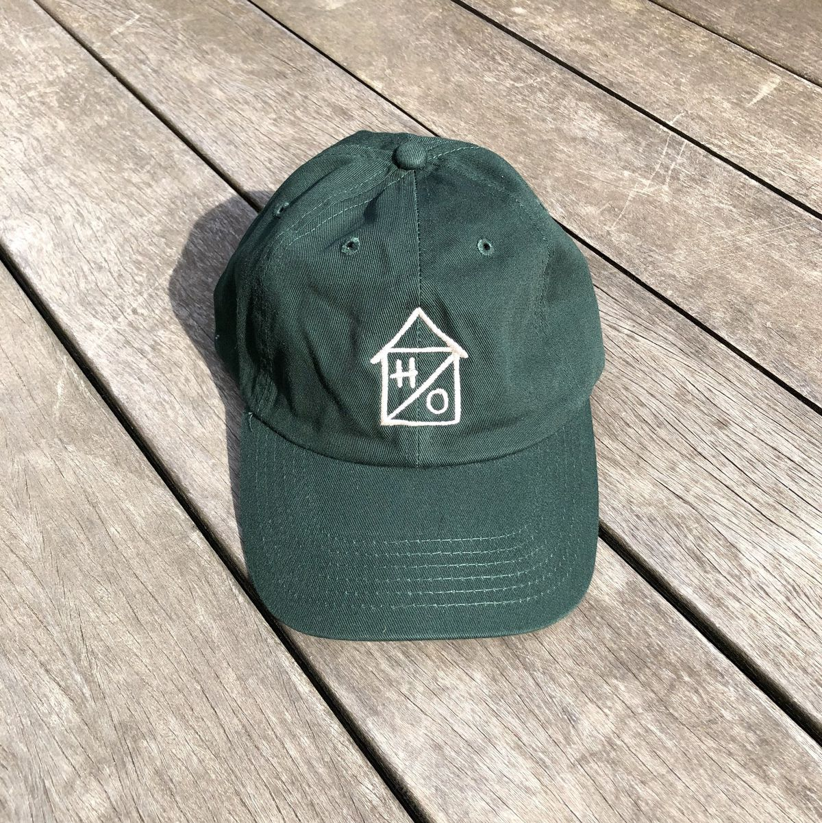 A green baseball-style hat with a tan Hideout logo stitched on the front.