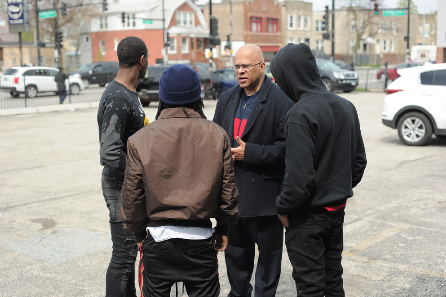Tio Hardiman, president of Violence Interrupters Inc., with three gang members near Central Park and Chicago avenues.   Victor Hilitski / Sun-Times