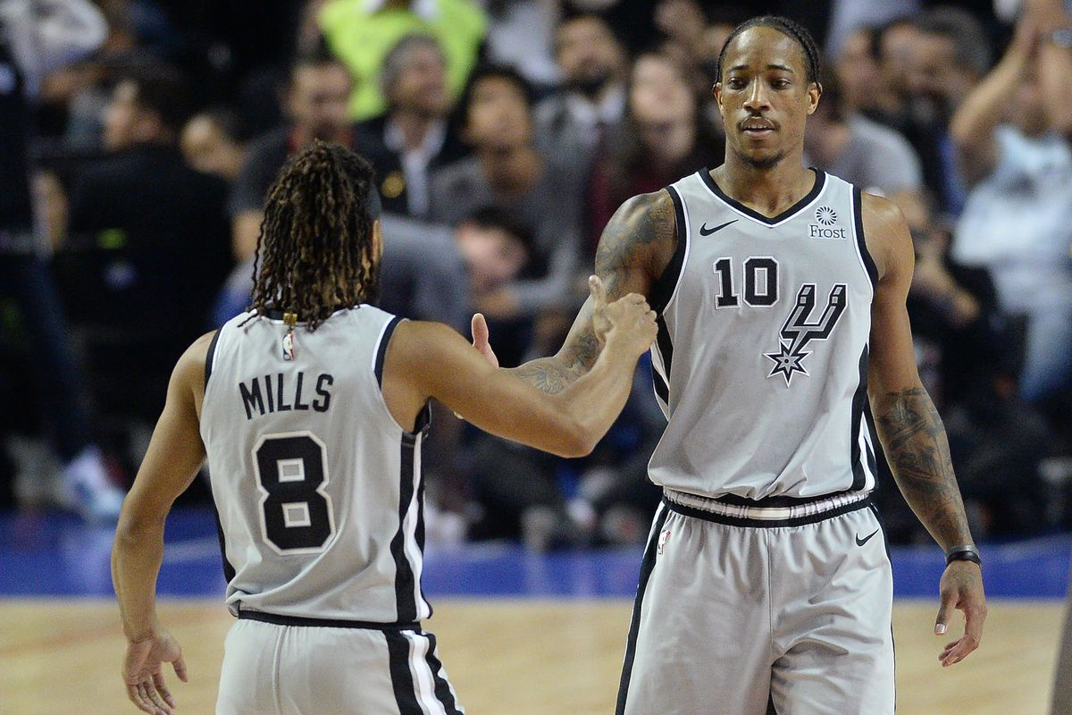 San Antonio Spurs guards Patty Mills and DeMar DeRozan celebrate after a basket against the Phoenix Suns during the fourth quarter at Mexico City Arena.