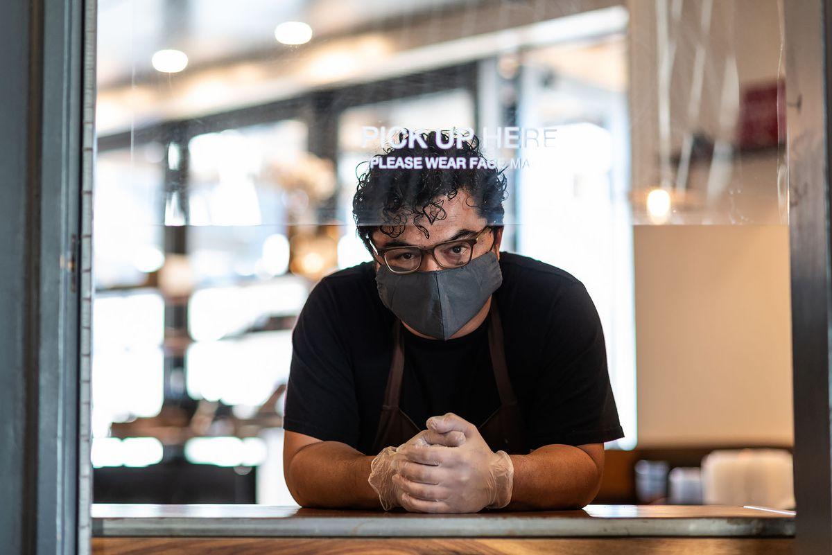 Carlos Salgado wearing a cloth mask at the pickup window at Taco Maria