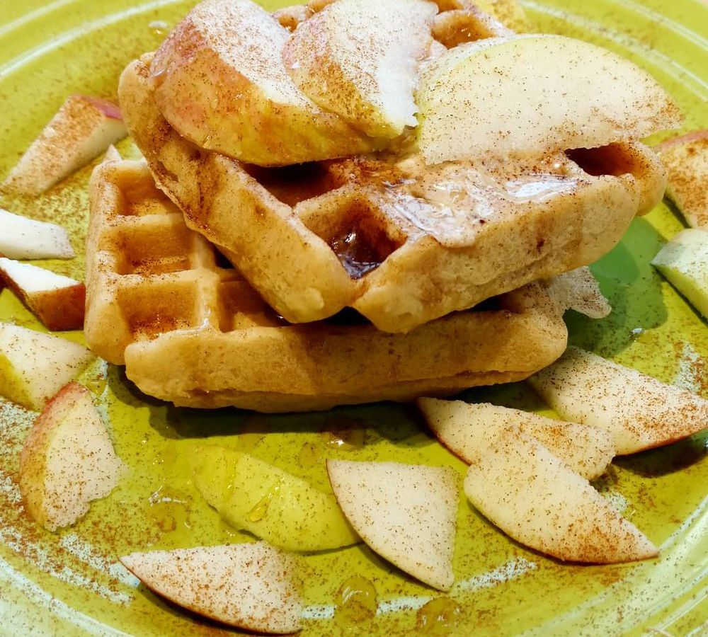 Gluten-free waffles sit on a green plate, and are topped with apples, syrup, and cinnamon.