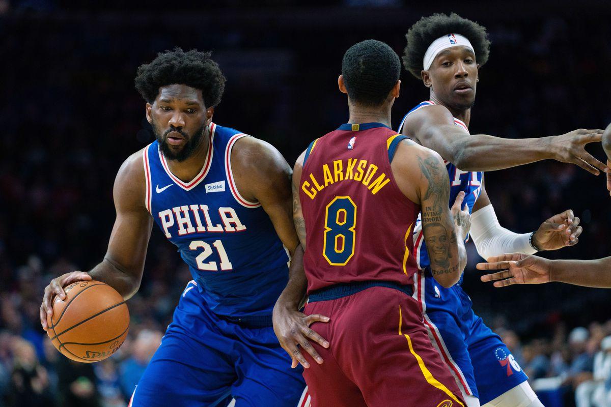 Philadelphia 76ers center Joel Embiid dribbles around Cleveland Cavaliers guard Jordan Clarkson in front of guard Josh Richardson during the first quarter at Wells Fargo Center.