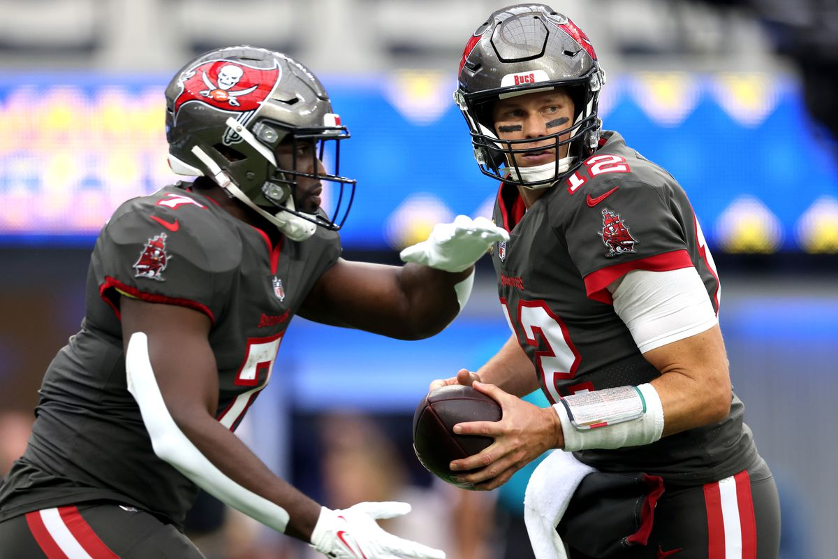 Tom Brady #12 of the Tampa Bay Buccaneers fakes a handoff to Leonard Fournette #7 during the first quarter in the game against the Los Angeles Rams at SoFi Stadium on September 26, 2021 in Inglewood, California.
