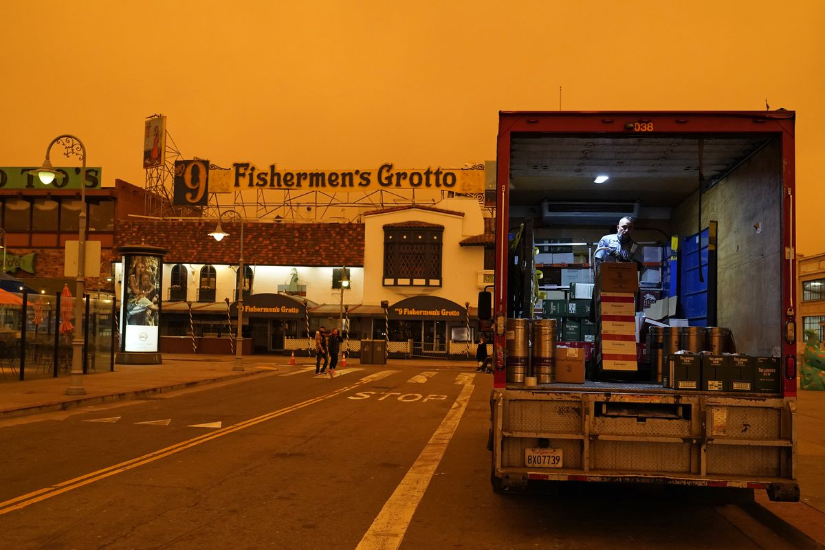 Under darkened skies from wildfire smoke, a truck driver unloads liquor at Fisherman's Wharf Wednesday, Sept. 9, 2020, in San Francisco.