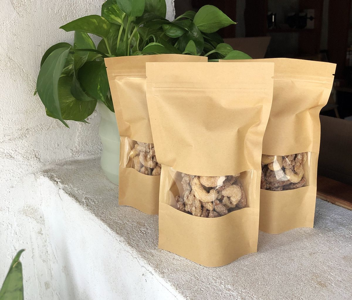 Three brown pouch packages of gravitas spiced nuts inside Castalia.