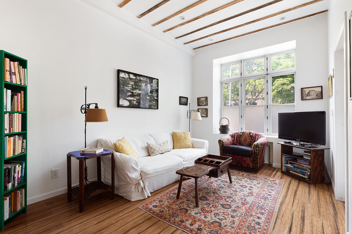 A living area with hardwood floors, a white couch, and a green book shelf.