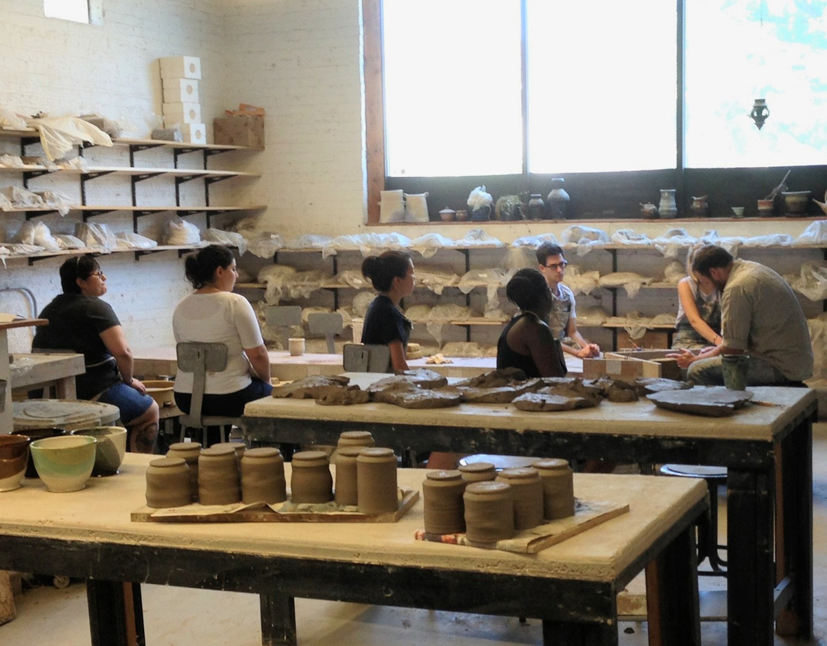 People sit at tables at a pottery class. The tables of full of various assorted pieces of pottery.