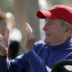 Former President George H. W. Bush applauds during a four-ball match at the Ryder Cup PGA golf tournament Saturday, Sept. 29, 2012, at the Medinah Country Club in Medinah, Ill.
