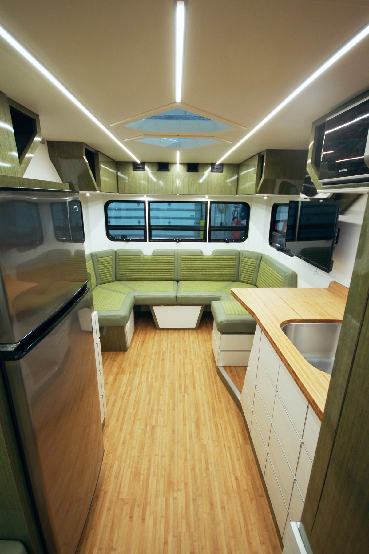 The interior of a vintage camper with wood floors, cream cabinets, bamboo kitchen counters, and a green u-shaped seating area.
