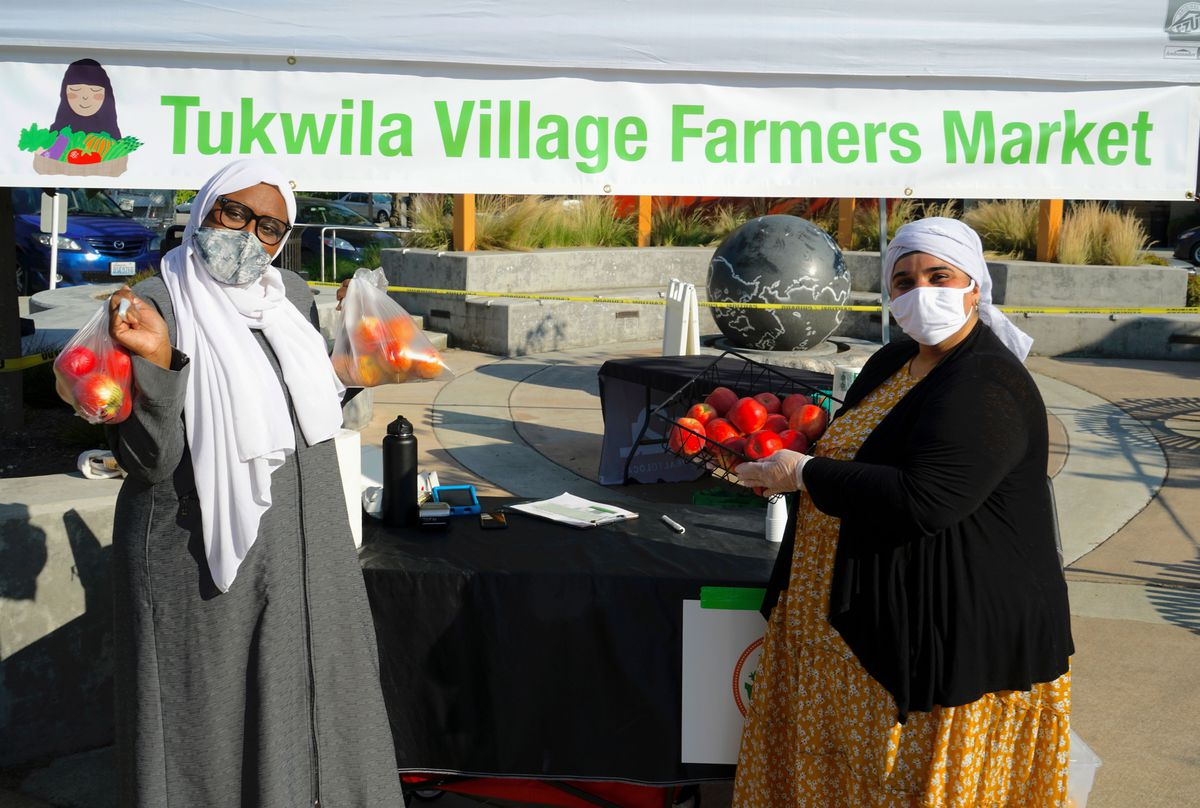 Two women in hijabs and head scarves hold up fruit under a green banner that says Tukwila Village Farmers Market.