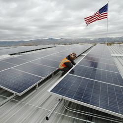 Hunt project manager Mike Carbine looks over a solar panel at Burton Lumber in Salt Lake City Wednesday, Nov. 6, 2013. Burton Lumber recently finished installing 4.5 acres of solar panels, the largest local privately owned solar project in Utah, which falls within the governors 10-year Energy Plan.