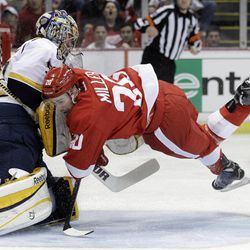 Detroit Red Wings left wing Drew Miller (20) runs into Nashville Predators goalie Pekka Rinne, left, of Finland, during the first period of Game 3 of an NHL hockey Stanley Cup first-round playoff series in Detroit, Sunday, April 15, 2012.
