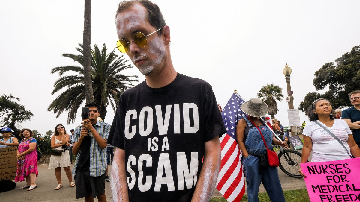 """A person wearing a T-shirt that reads, """"Covid is a scam."""""""