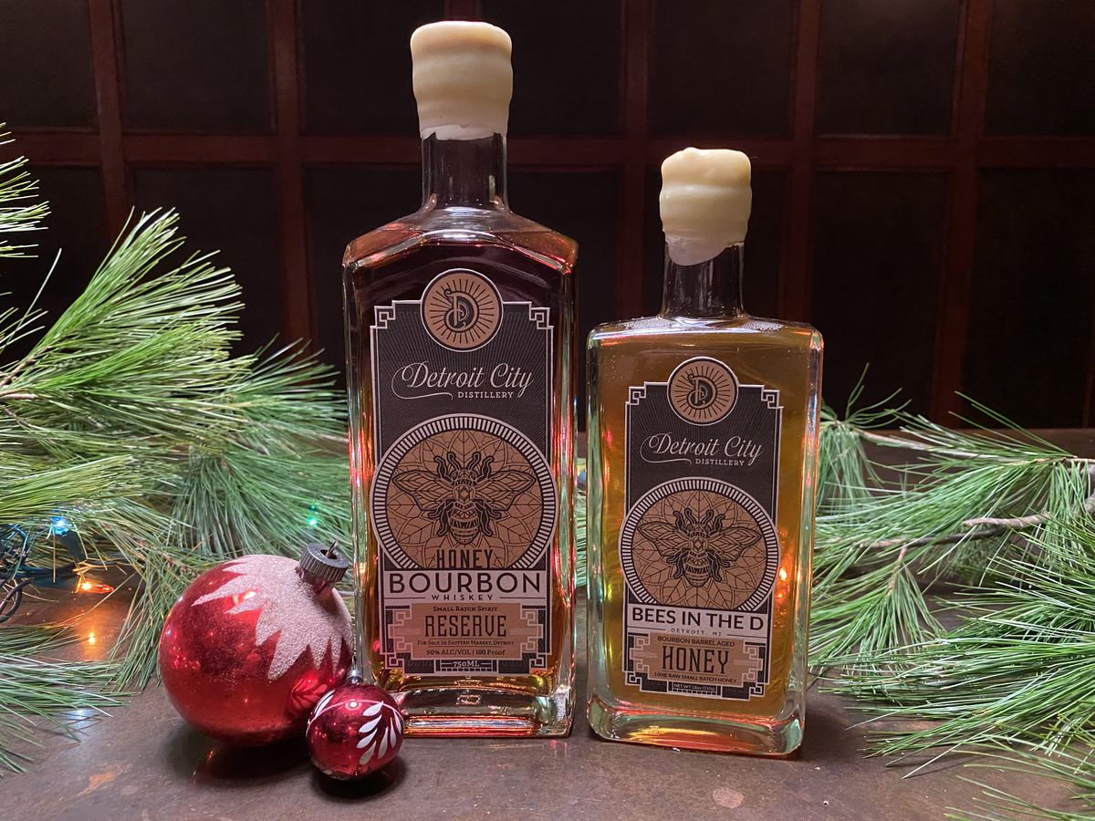 A bottle of Honey Bourbon Reserve and a Smaller Bottle of Bees in the D Honey Bourbon next to some pine tree needles and red Christmas ornaments.