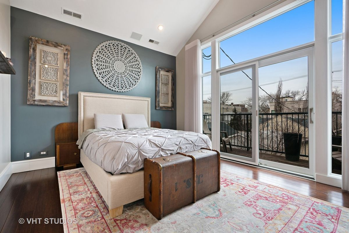 A bed against an accent wall next to a floor-to-ceiling window on a pink and white rug.