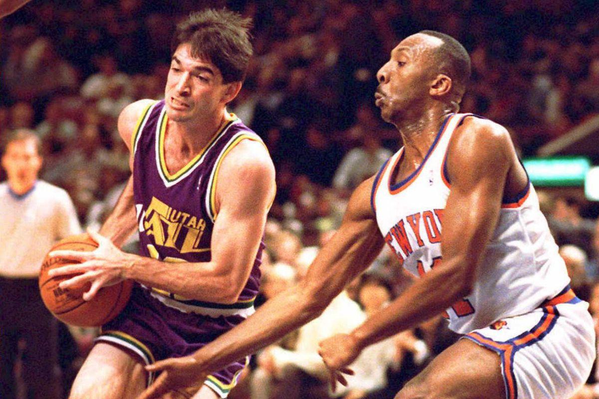 Utah Jazz John Stockton (L) charges to the basket