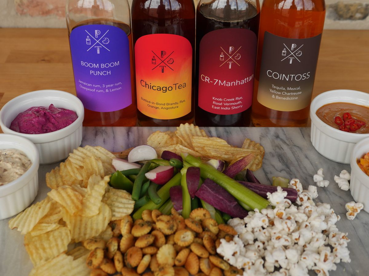 A platter of snacks in front of four glass bottles filled with cocktails.