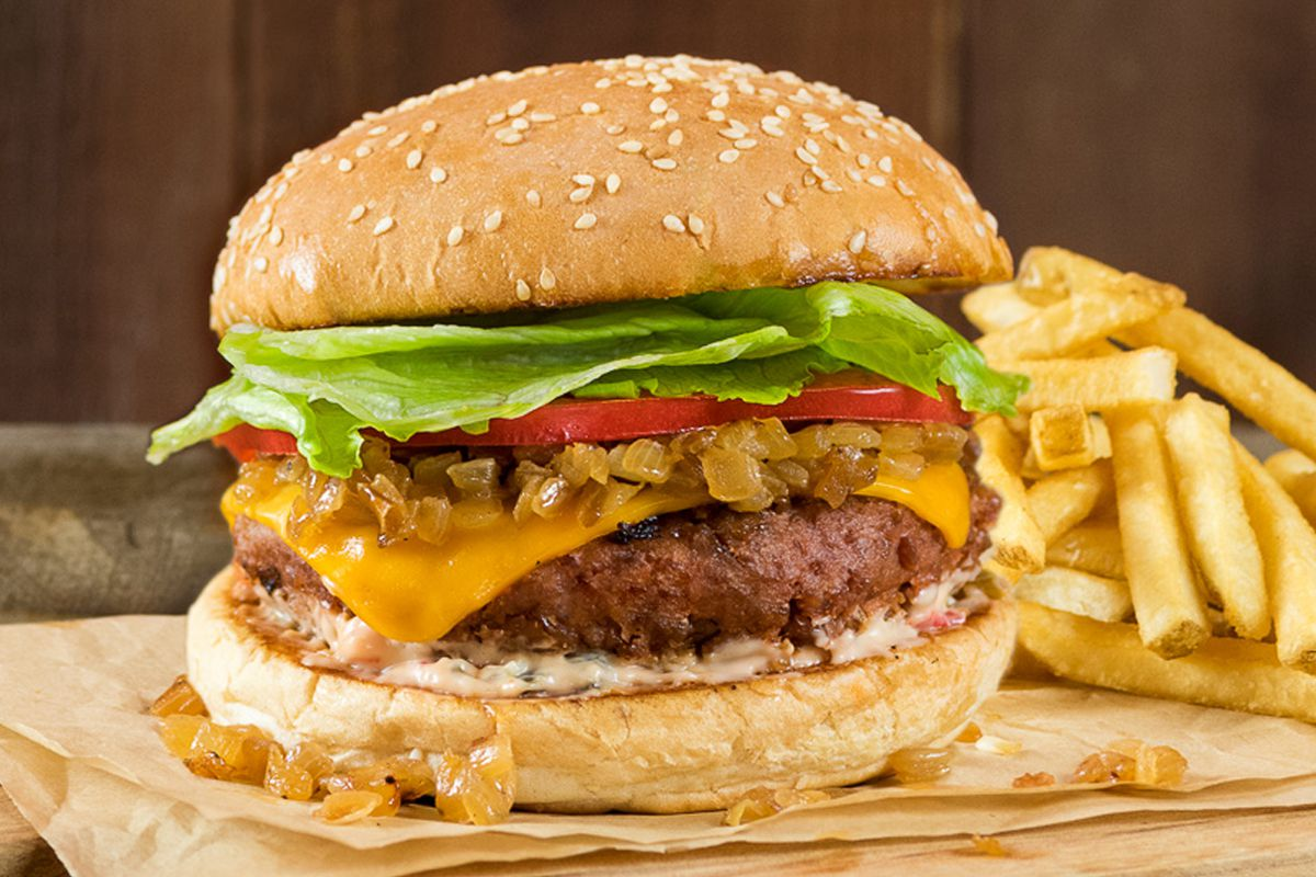 A meat-free burger with cheese, lettuce, tomatoes, on a sesame seed bun with fries.