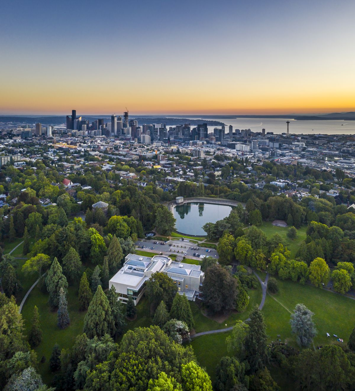 An aerial photograph of a park at sunset. In the middle of many trees, there's a top of a building that combines older (forward) and newer (toward the camera) construction. There's a large reservoir in front of it and tall buildings in the background.