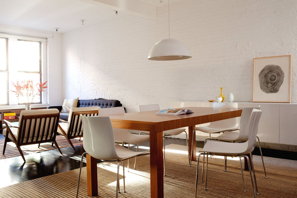 A dining table with six white chairs.