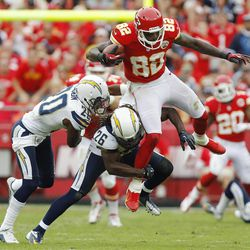Kansas City Chiefs wide receiver Dwayne Bowe (82) is tackled by San Diego Chargers strong safety Atari Bigby (26) and cornerback Antoine Cason (20) during the first half of an NFL football game at Arrowhead Stadium in Kansas City, Mo., Sunday, Sept. 30, 2012.