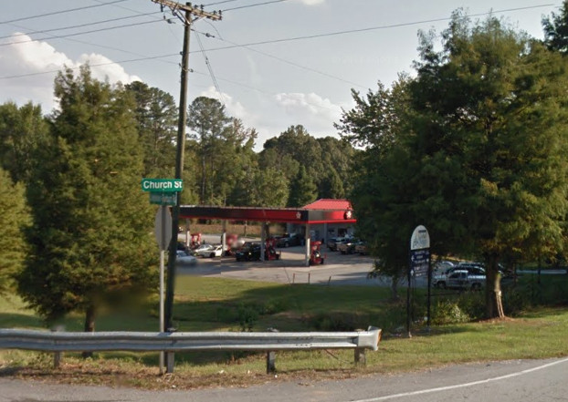 A gas station with a red awning. There are trees surrounding the gas station.