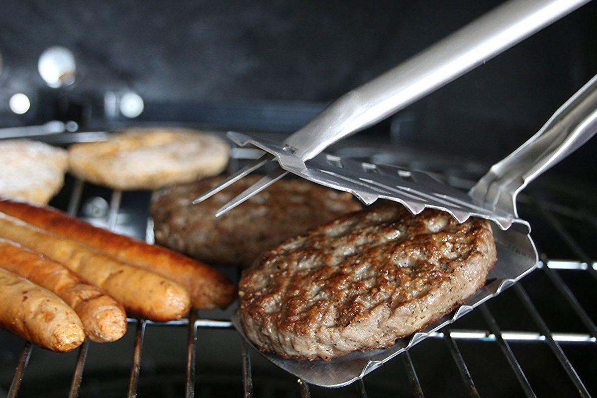 The Stingray BBQ tool flipping a hamburger on a grill