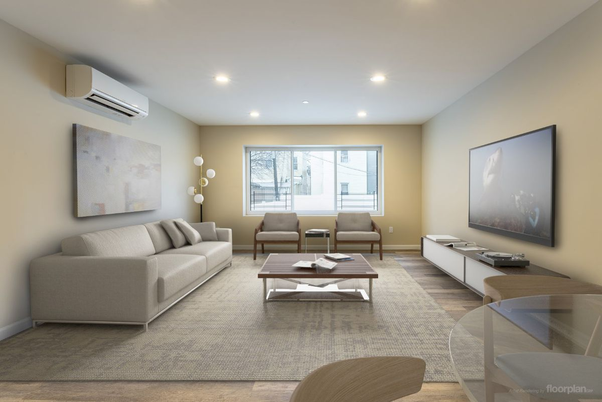 A living room area with a couch, two chairs, a coffee table, a TV on the wall, and hardwood floors.