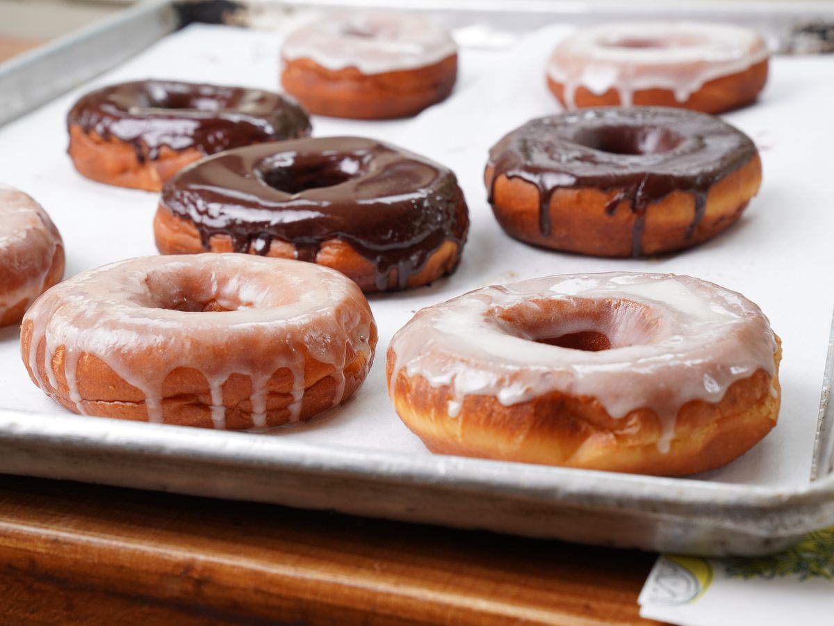 A tray of just-glazed doughnuts rests on a kitchen countertop. A half-dozen of the baked goods appear with white and chocolate forsting.