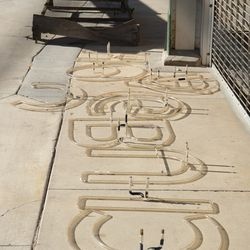 1:40 p.m. Neon letters from the marquee, laid out on the ground in front of Gate F -