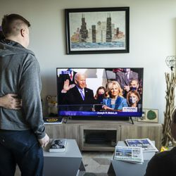 Matt Schreck, 43, his husband, Fernando Gutierrez, 41, and their friend Brian Dowling, 39, watch the inauguration ceremony for President Joe Biden and Vice President Kamala Harris from Schreck and Gutierrez's South Loop home, Wednesday morning, Jan. 20, 2021.