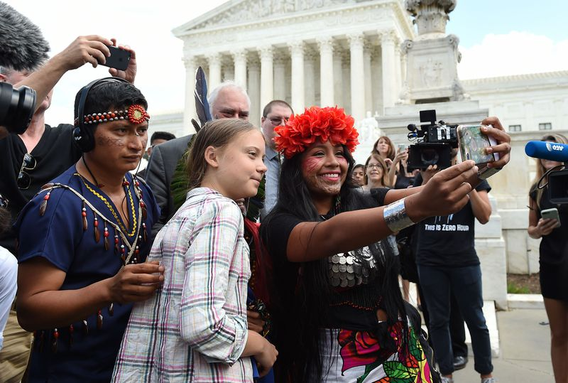 Militza Flaco (R) from the Global Alliance of Territorial Communities Guardians of the Forest takes a selfie with Swedish teen climate activist Greta Thunberg in front of the Supreme Court to support the children's climate lawsuit against the US
