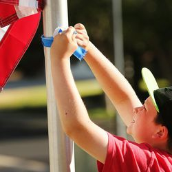 Luke Wilhite  ties a ribbon on a flag pole as community members gather to tie ribbons and write messages to the Rackley family and first responders of the murder-suicide along Alta Canyon Drive in Sandy on Saturday, June 10, 2017.