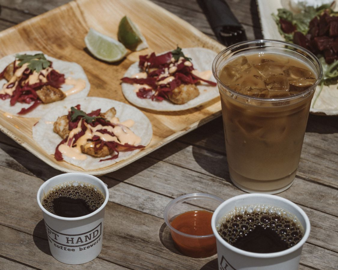 Plates of food, cups of coffee, and some containers of sauces placed on a wooden table