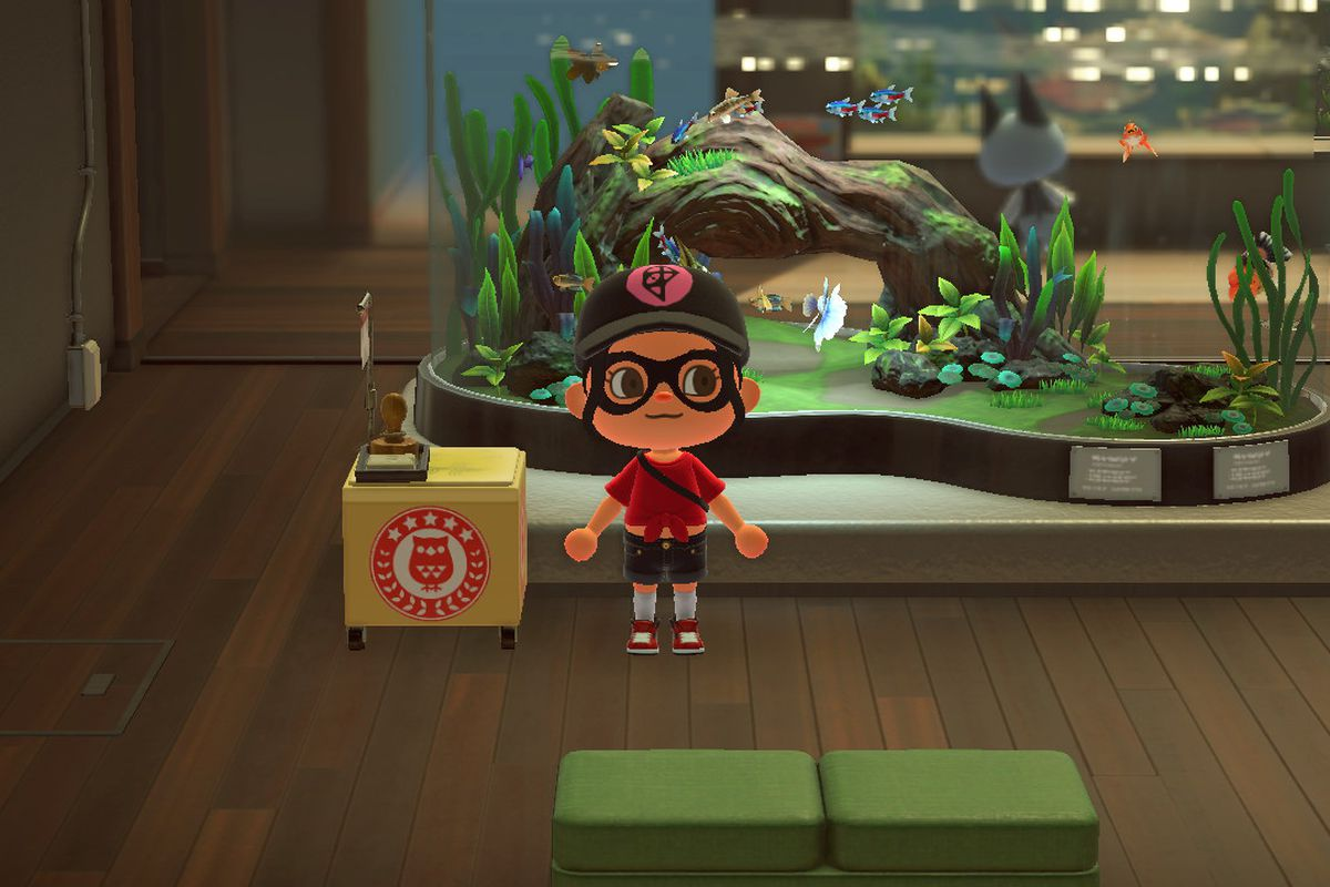 An Animal Crossing villager stands in front of a fish tank with a stamp table near it