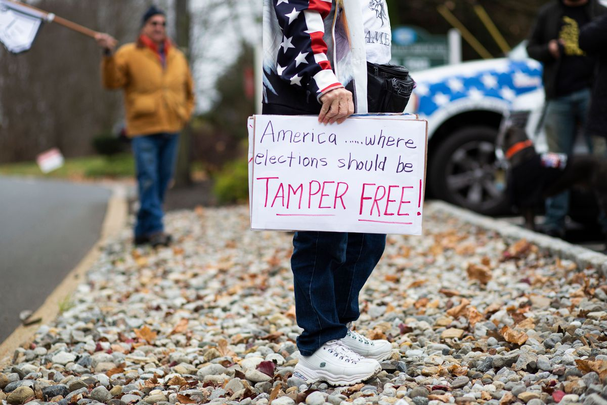 "A person holds a placard that reads ""America, where elections should be tamper free!"" as President Trump's supporters gather during a car rally called Stop the Steal on November 22, 2020, in Long Valley, New Jersey."
