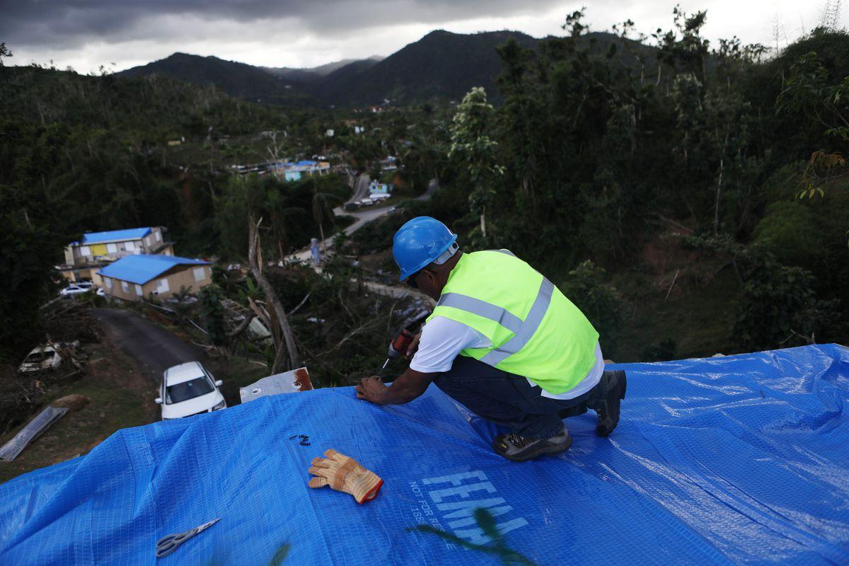 A contractor applies a FEMA tarp to a home damaged by Hurricane Maria in Puerto Rico.