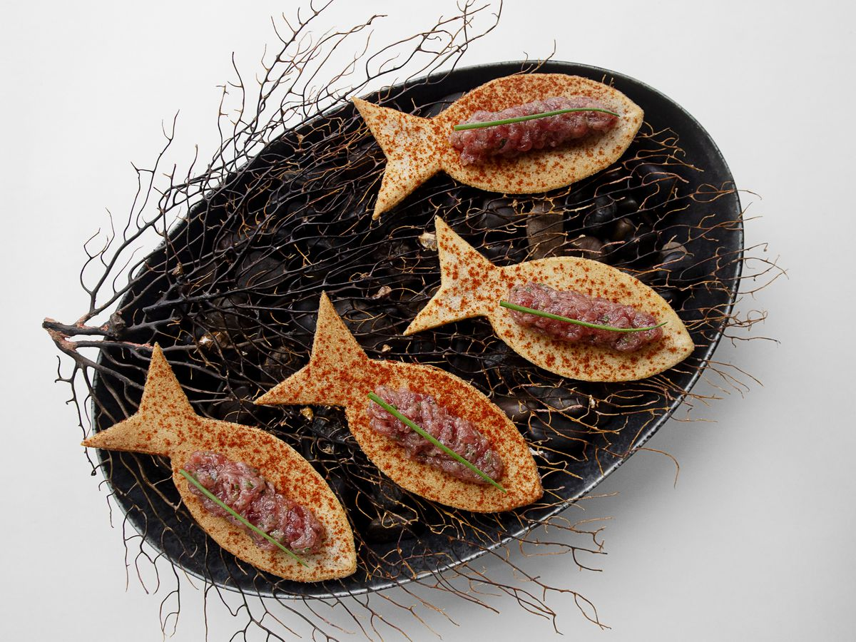 Four fish-shaped biscuits sit on a dark, charcoal-colored plate