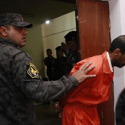 A handcuffed suspect is escorted at the federal police headquarters in Baghdad, Iraq, Sunday, April 8, 2012. Iraqi officials say they have arrested a ring of insurgents allegedly involved in attacks in Baghdad.
