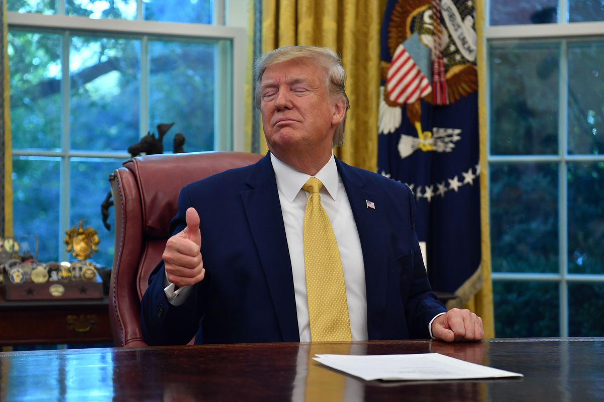 President Donald Trump sitting behind his desk in the Oval Office making a thumbs-up gesture.