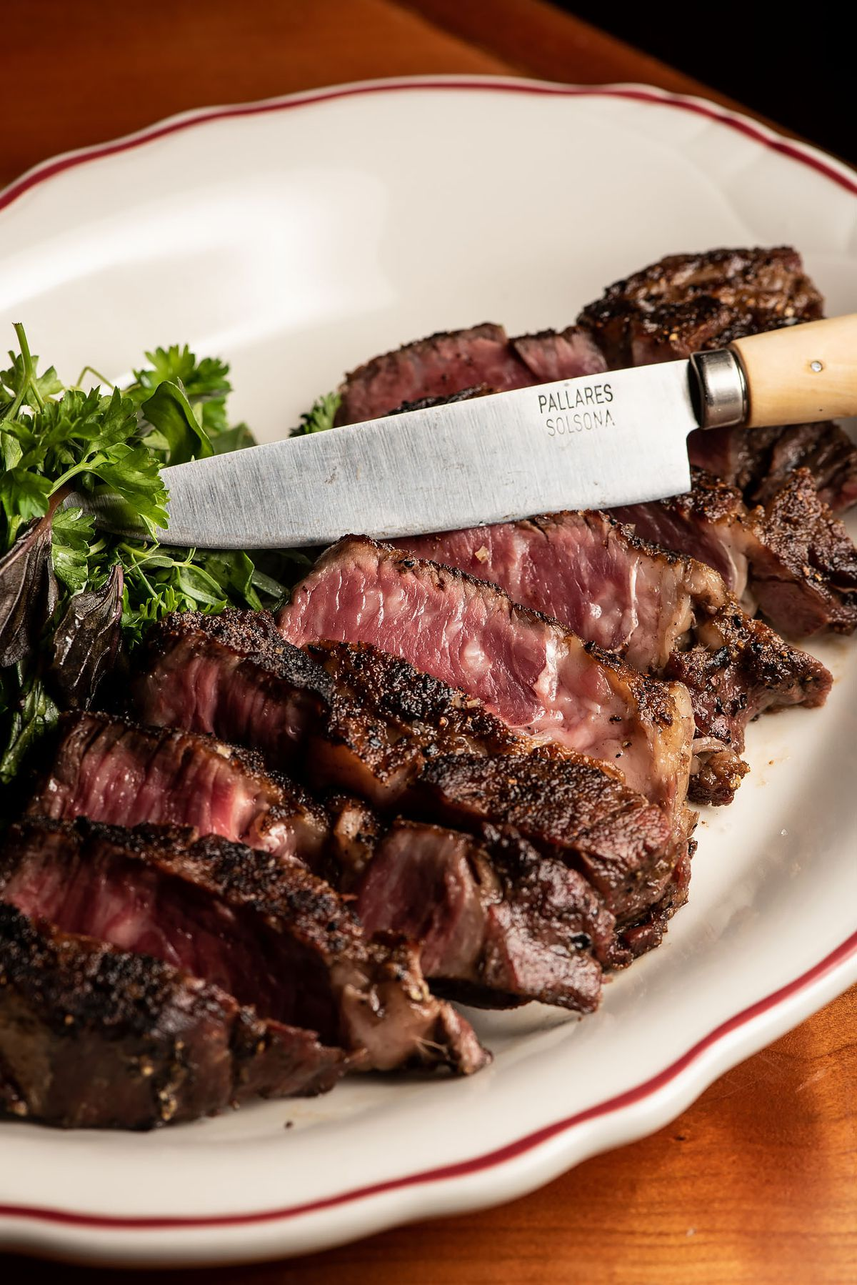 A rare steak cut into section, with knife on top.