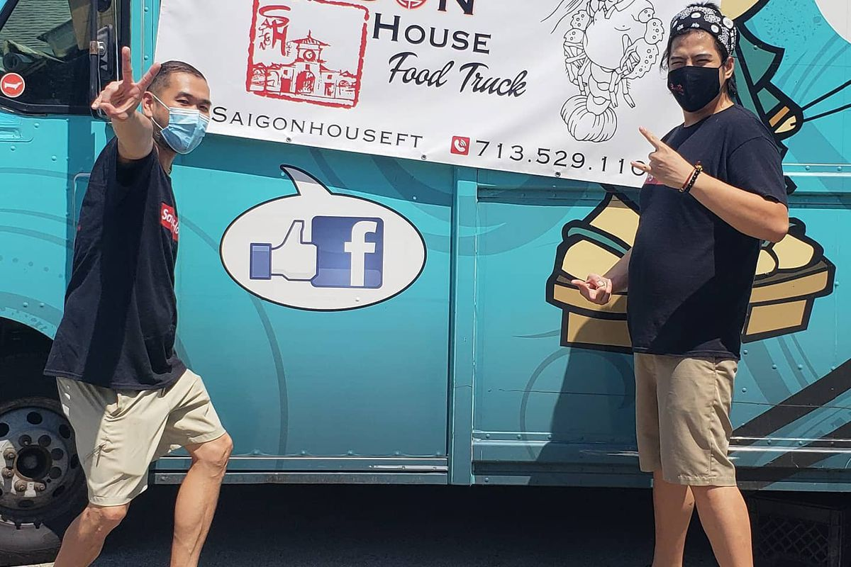 two masked duded standing in front of a blue food truck