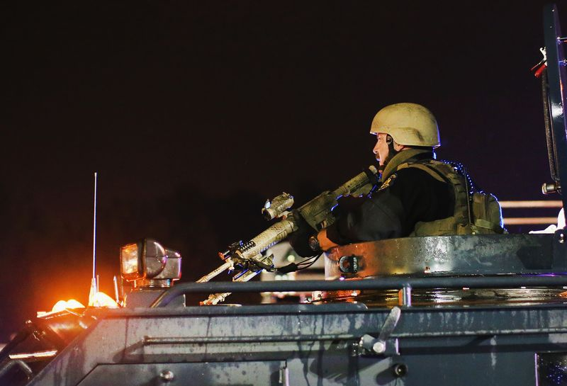 A police officer sits in an armored vehicle.