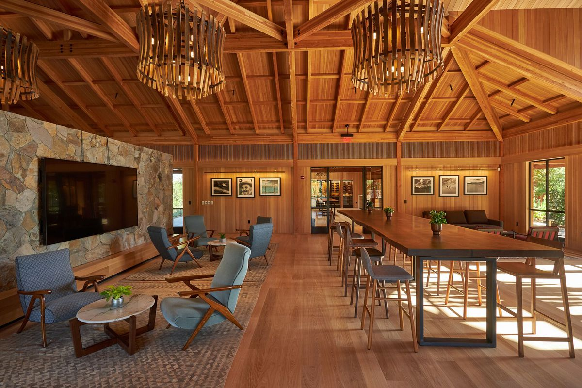 A wood-paneled room with wine barrel lamps.