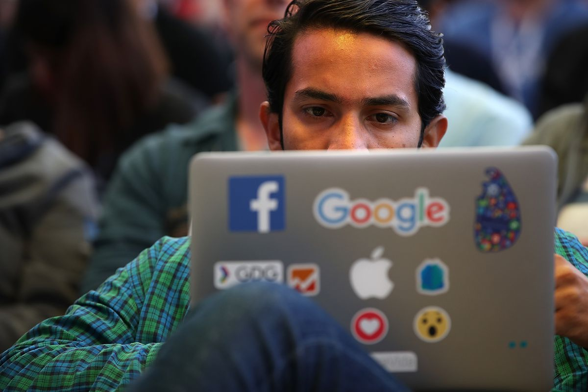 A man looks at his laptop screen; the laptop lid is covered in stickers, including for Facebook and Google.