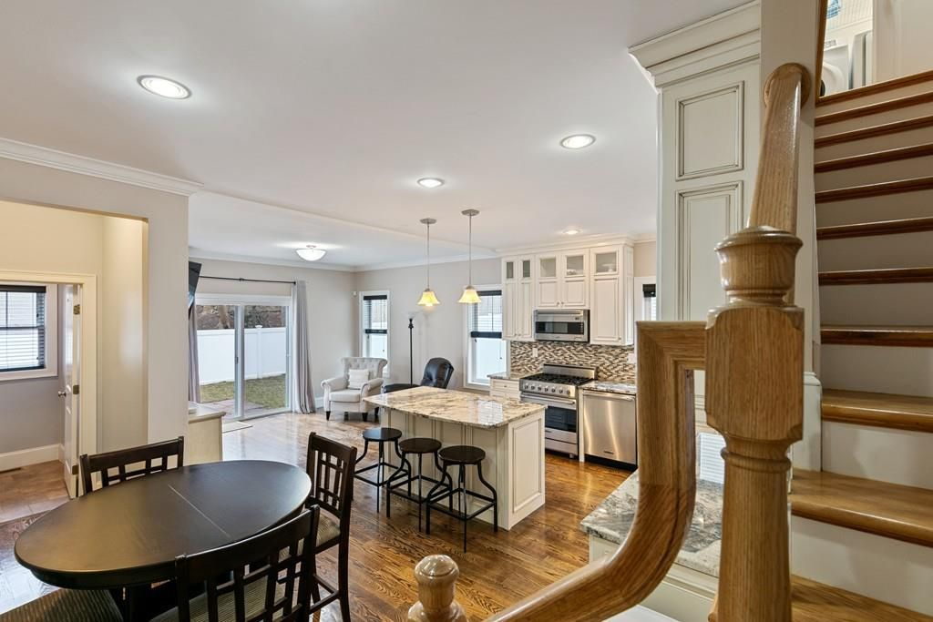 The view of an open dining room and kitchen with furniture from over a stairwell banister.