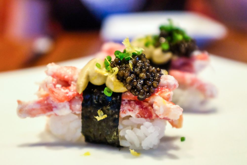 Several pieces of lobster sushi topped with caviar sit on a white plate